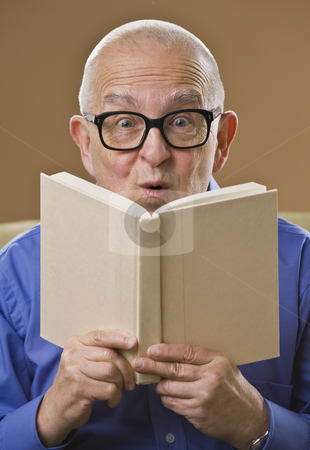 Silly senior man reading book. stock photo, Silly senior man with glasses reading book, looking at the camera. Vertical. by Jonathan Ross