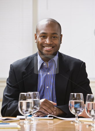 African American male smiling. stock photo, African American male sitting at desk with water, smiling at the camera. Vertical by Jonathan Ross