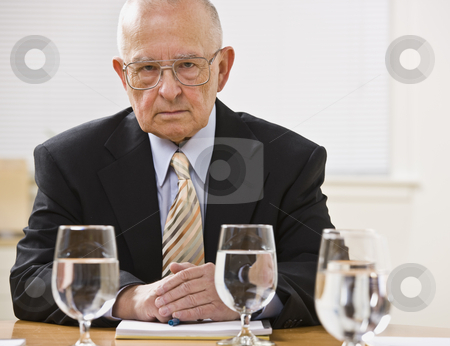 Man at Desk in Office stock photo, An elderly businessman is seated at a desk in an office and is looking at the camera.  Horizontally framed shot. by Jonathan Ross