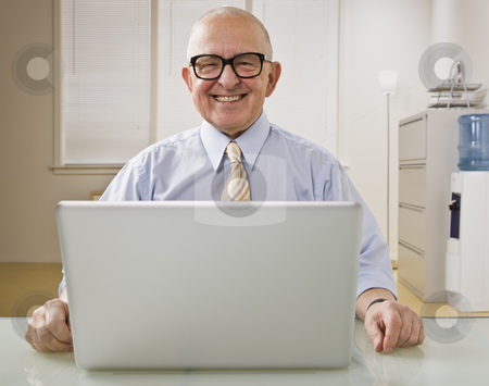 Man on Laptop stock photo, An elderly man is on a laptop in an office.  He is smiling at the camera.  Horizontally framed shot. by Jonathan Ross