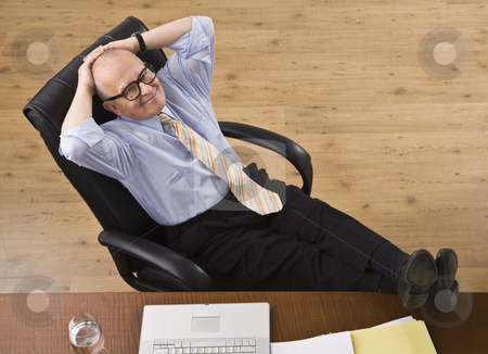Attractive senior business man relaxing. stock photo, Attractive senior business man relaxing with feet on desk, reclining in chair, smiling at camera. Horizontal by Jonathan Ross