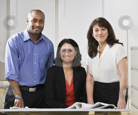 Business team posing for picture. stock photo, Business team posing for picture, Two white woman and one african american man standing at desk.Horizontal by Jonathan Ross