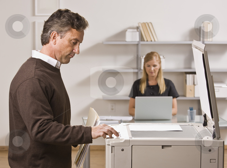 Man Making Copies stock photo, A businessman is making copies in an office.  There is a woman behind him at a desk.  He is looking away from the camera.  Horizontally framed shot. by Jonathan Ross