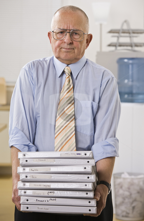 Man Holding Binders stock photo, An elderly businessman is holding a stack of binders.  He is looking at the camera.  Vertically framed shot. by Jonathan Ross