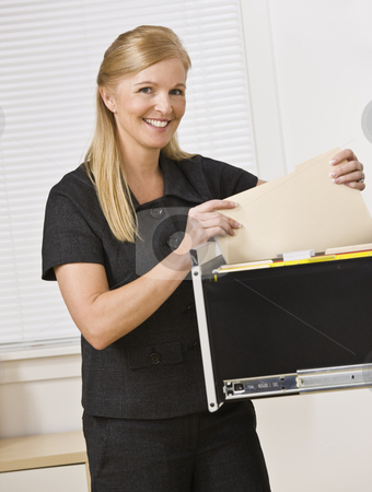 Woman Looking Through Filing Cabinet stock photo, A businesswoman is looking through a filing cabinet and smiling at the camera.  Vertically framed shot. by Jonathan Ross