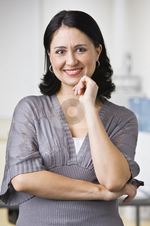 Woman in Office stock photo, A young businesswoman is standing in an office and smiling at the camera.  Vertically framed shot. by Jonathan Ross