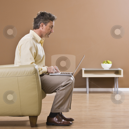 Man on Laptop stock photo, A businessman is seated on a couch and working on a laptop.  He is looking away from the camera.  Square framed shot. by Jonathan Ross
