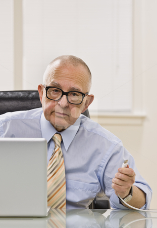 Man on Computer stock photo, An elderly man is working on a computer in an office.  He is looking at the camera.  Vertically framed shot. by Jonathan Ross