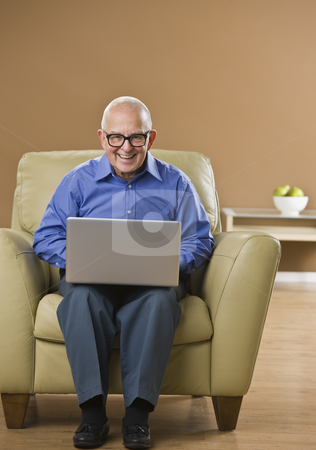 Man on Laptop stock photo, An elderly man is seated in a room and is working on a laptop.  He is smiling at the camera.  Vertically framed shot. by Jonathan Ross