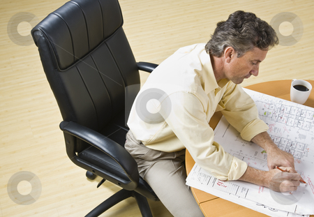 Attractive male with drawings. stock photo, Attractive male siting at desk with drawings of home. Looking at desk. Horizontal by Jonathan Ross