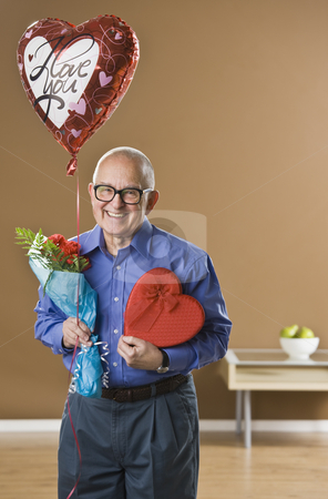 Man with Valentines Presents stock photo, An elderly man is holding valentines gifts.  He is smiling at the camera.  Vertically framed shot. by Jonathan Ross
