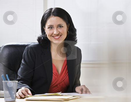 Woman in Office stock photo, A young businesswoman is seated at a desk in an office and is smiling at the camera.  Horizontally framed shot. by Jonathan Ross