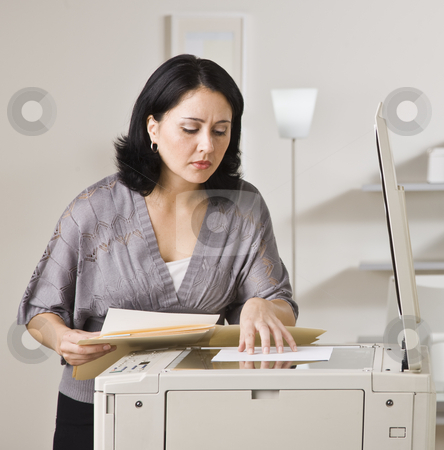 Attractive asian woman making copy. stock photo, Attractive asian woman making copy on copy machine in office. Looking at paper on machine. Square. by Jonathan Ross