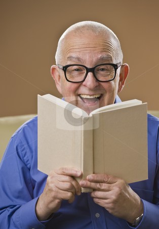 Laughing senior male reading a book stock photo, Laughing senior male reading a book on a couch. Vertical by Jonathan Ross