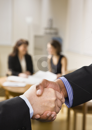 People Shaking Hands in Office stock photo, Two businesspeople are shaking hands in an office.  Two office ladies are seated at a desk in the background.  Vertically framed shot. by Jonathan Ross