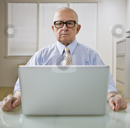 Man on Laptop stock photo, An elderly businessman is working on a laptop in an office.  He is looking at the camera.  Square framed shot. by Jonathan Ross