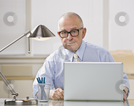 Older man on laptop. stock photo, Older bald man with glasses on laptop. Desk lamp lighting from above. Horizontal. by Jonathan Ross