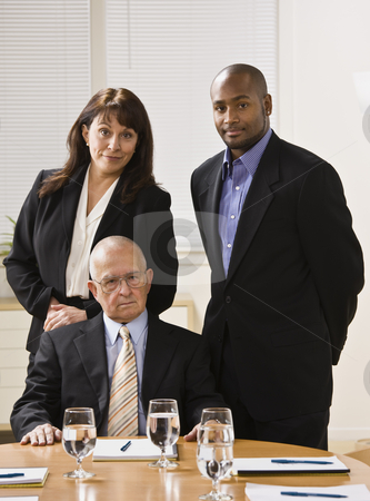 Three business people posing. stock photo, Three business people posing for photo. African American male and woman standing, male senior sitting in front of them. Vertical. by Jonathan Ross
