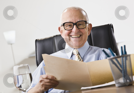 Elderly Business Man Smiling stock photo, An elderly business man seated in an office and smiling.  He is holding a file folder and is wearing glasses.  Horizontally framed shot. by Jonathan Ross