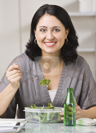 Woman Eating Lunch stock photo, A young woman is seated at a desk in an office and is eating her lunch.  She is smiling at the camera.  Vertically framed shot. by Jonathan Ross