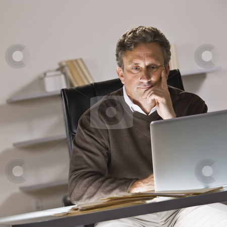 Man on Laptop stock photo, A businessman is working on a laptop in an office.  He is looking away from the camera.  Square framed shot. by Jonathan Ross