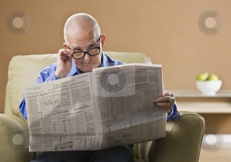 Elderly Man Reading Newspaper stock photo, An elderly man is sitting in his living room reading a newspaper.  He is looking at the camera.  Horizontally framed shot. by Jonathan Ross