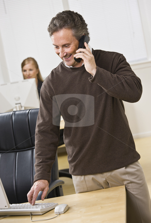Attractive business man on phone. stock photo, Attractive business man standing over keyboard while chatting on the phone. Woman peering in back. Looking at the computer screen. Vertical. by Jonathan Ross