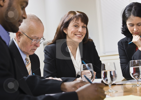 Business People in Meeting stock photo, A group of business people are seated around a desk in a meeting.  They are looking away from the camera.  Horizontally framed shot. by Jonathan Ross