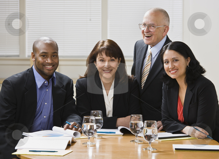 Four business workers smiling stock photo, Four business workers, two men and two women, sitting at desk smiling at camera. Horizontal by Jonathan Ross