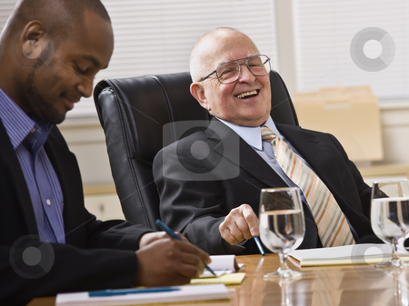 Men in Business Meeting stock photo, An elderly man and a young businessman are seated together at a desk in an office.  They are laughing and looking away from the camera.  Horizontally framed shot. by Jonathan Ross
