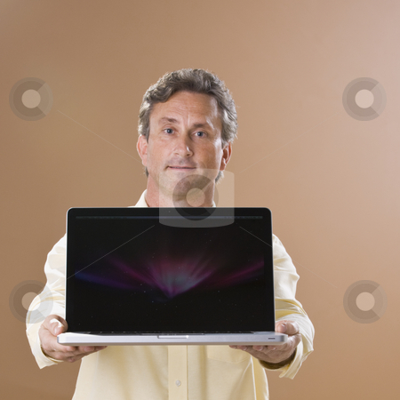 Man Holding Laptop stock photo, A man is holding a laptop out in front of him and looking at the camera.  Square framed shot. by Jonathan Ross