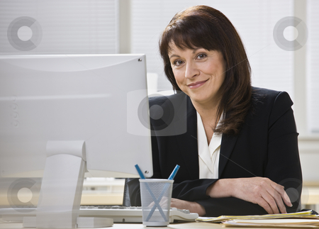 Attractive business woman smiling. stock photo, Attractive business woman stting at desk behind computer monitor smiling at camera. Horizontal. by Jonathan Ross