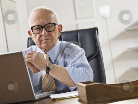 Elderly Man on Laptop stock photo, An elderly man is seated at a desk in front of a laptop and is looking at the camera.  Horizontally framed shot. by Jonathan Ross
