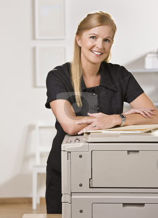 Woman in Office stock photo, A businesswoman is standing in an office near the copy machine.  She is smiling at the camera.  Vertically framed shot. by Jonathan Ross