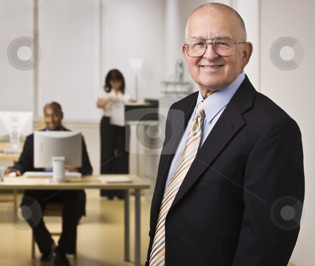 Business People Working in Office stock photo, A group of business people are working in an office.  The men are smiling at the camera and the woman is looking through a filing drawer.  Horizontally framed shot. by Jonathan Ross