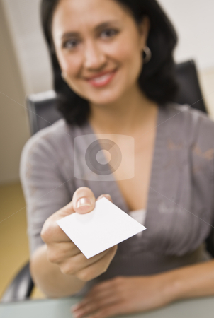 Woman Holding Out Business Card stock photo, A young businesswoman is holding a business card out in front of her and smiling at the camera.  Vertically framed shot. by Jonathan Ross