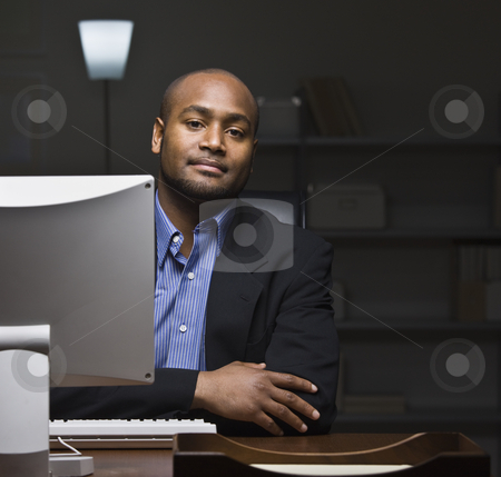 Man at Computer Desk stock photo, A young businessman is seated at a desk and is working on a computer.  He is looking at the camera.  Square framed shot. by Jonathan Ross
