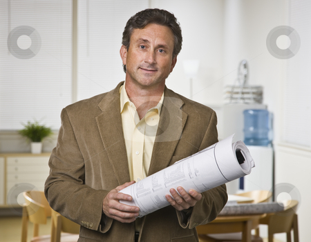 Man Holding Blueprints stock photo, A businessman is standing in an office, holding blueprints, and looking at the camera.  Horizontally framed shot. by Jonathan Ross