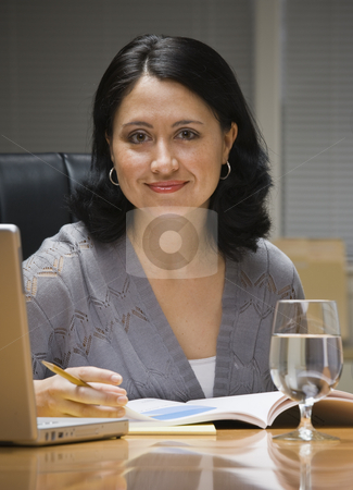 Woman on Computer stock photo, A young businesswoman is sitting at a desk with a computer.  She is smiling at the camera.  Vertically framed shot. by Jonathan Ross
