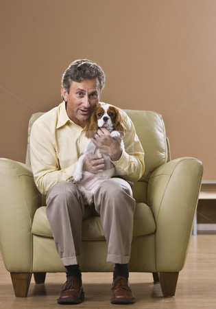 Man Holding Puppy stock photo, A man is seated in a chair in a room and is holding a puppy.  He is smiling at the camera.  Vertically framed shot. by Jonathan Ross