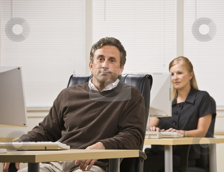 Man and Woman Working in Office stock photo, A businessman and woman are working in an office on computers.  The woman is looking at the computer screen and the man is looking at the camera.  Horizontally framed shot. by Jonathan Ross
