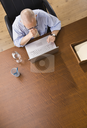 Man on Laptop stock photo, An elderly businessman is working on a laptop in an office.  He is looking away from the camera.  Vertically framed shot. by Jonathan Ross