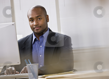 Man on Computer stock photo, A young businessman is working on a computer in an office.  He is smiling at the camera.  Horizontally framed shot. by Jonathan Ross