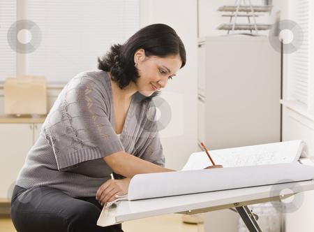 Woman Working on Blueprints stock photo, A young woman is sitting at a desk in an office and is working on blueprints.  She is looking away from the camera.  Horizontally framed shot. by Jonathan Ross