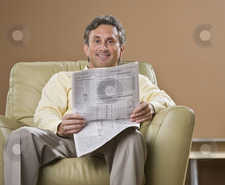 Man Reading Newspaper stock photo, An older man is sitting in a chair and reading a newspaper.  He is smiling at the camera.  Horizontally framed shot. by Jonathan Ross