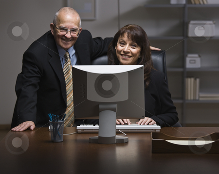 Man and Woman Working in Office stock photo, An elderly businessman and a younger businesswoman are working together on a computer in an office.  They are smiling at the camera.  Horizontally framed shot. by Jonathan Ross