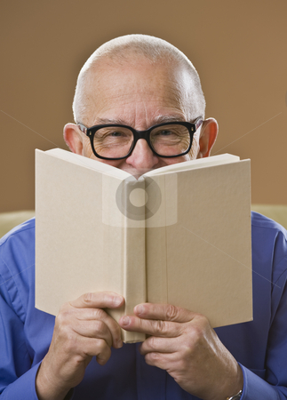 Man Reading Book stock photo, An elderly man is holding up a book and looking at the camera.  Vertically framed shot. by Jonathan Ross