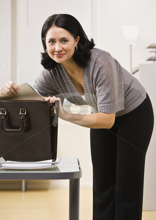 Attractive brunette looking in briefcase. stock photo, Attractive brunette searching in briefcase, looking at camera. Vertical by Jonathan Ross