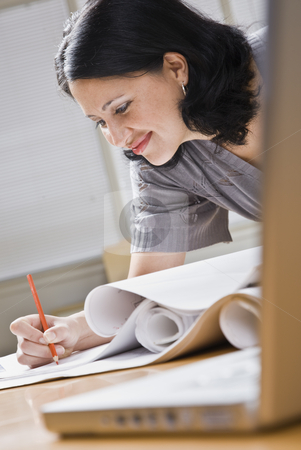 Attractive woman drawing. stock photo, Attractive woman leaning over desk drawing on sketches. Vertical by Jonathan Ross