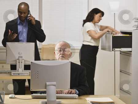 Business People Working in Office stock photo, A group of business people are working in an office.  Horizontally framed shot. by Jonathan Ross